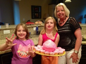 Evie and Mary showing off the homemade birthday cake - cupcake that they made with Grandma!