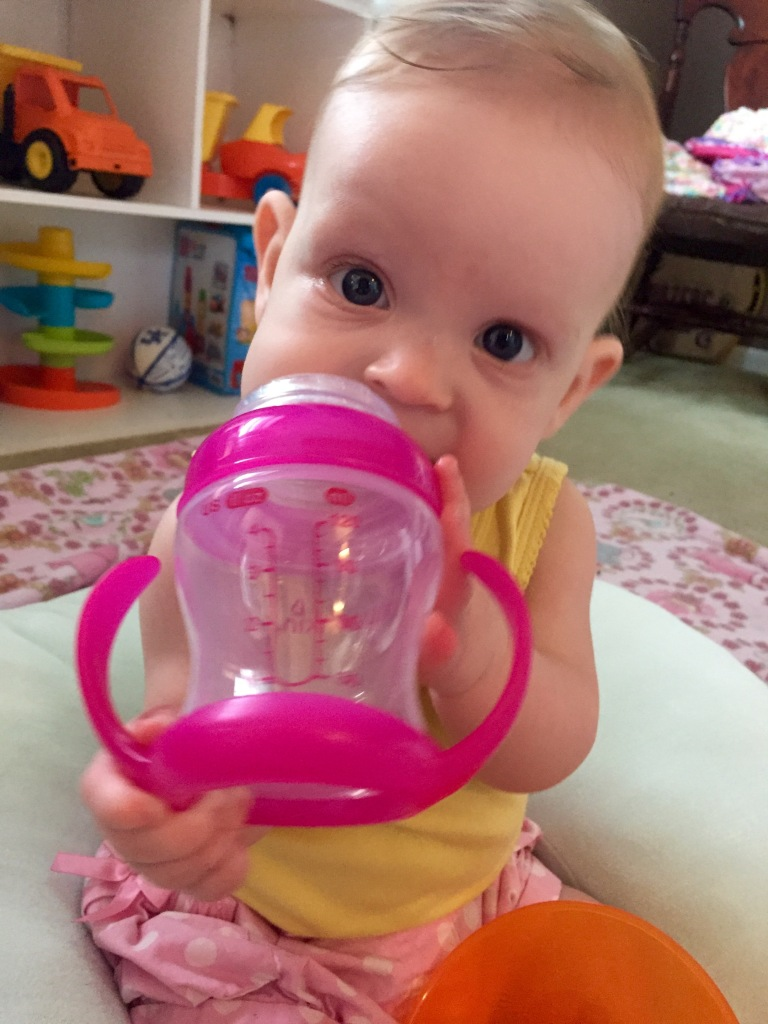 Working on holding her sippy!