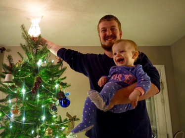 Helping daddy put the angel on top of the tree for the first time!
