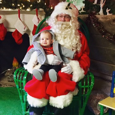 Meeting Santa for the first time!.. we may have bribed her with puffs to get her to sit with him lol